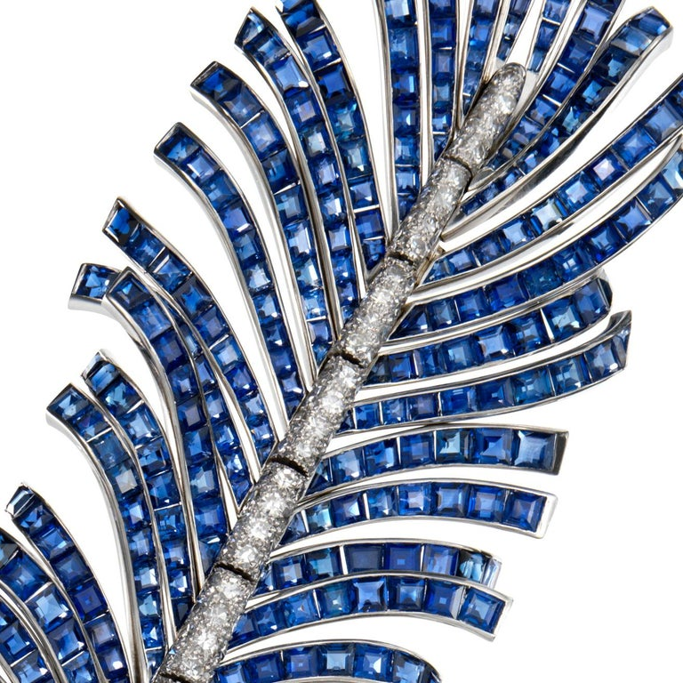 A brooch in the form of a feather realistically designed with highly flexible and articulated calibré-cut sapphire vane originating from a shaped pavé-set diamond shaft; mounted in platinum • 129 diamonds, total weighing approximately 2.60 carats •
