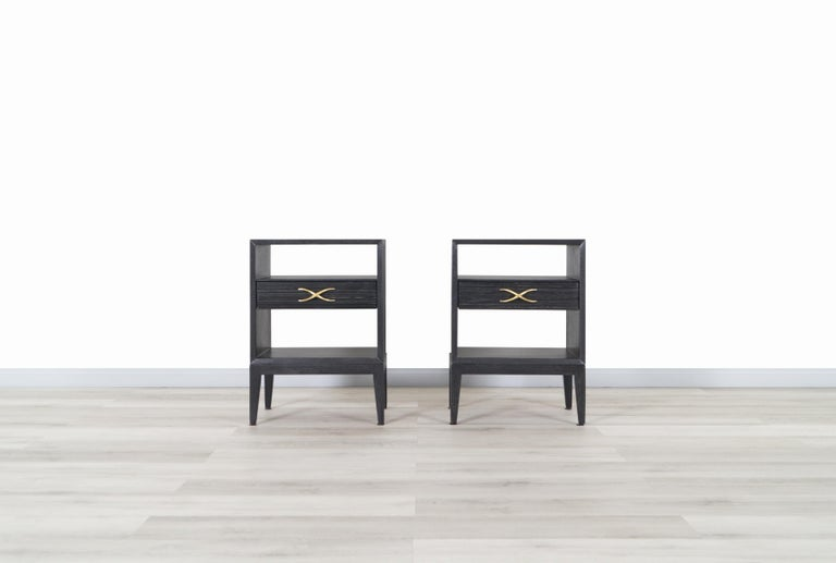 A pair of rare vintage nightstands / bedside tables designed by Paul Frankl and manufactured for Brown Saltman in the United States. These gorgeous nightstands are professionally restored in a black Cerused oak finish. Each nightstand features a