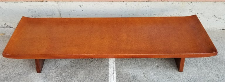 A Paul Frankl cork top coffee table or bench, circa 1940s. Asian influence design with curved table top. Base crafted in solid hardwood. Top refinished in lacquer.   Paul Frankl: 1886-1958  Paul T. Frankl was an Art Deco furniture designer and