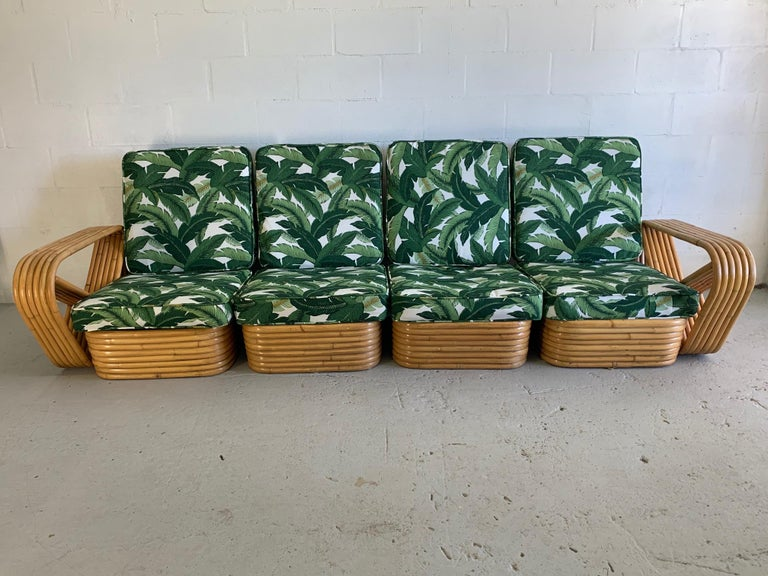 Four-piece modular rattan Paul Frankl style pretzel sofa features 6-strand frame and newly upholstered tropical palm leaf fabric. Very good condition both structurally and cosmetically with minor imperfections consistent with age. Can be arranged