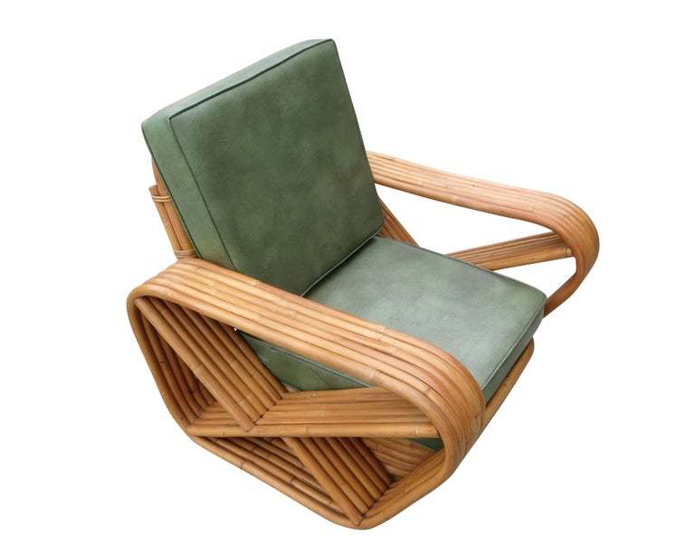 Designed in the manner of Paul Frankl, this six-strand, rattan lounge chair features square pretzel arms and a Classic stacked base. Included is the matching stacked rattan Ottoman.