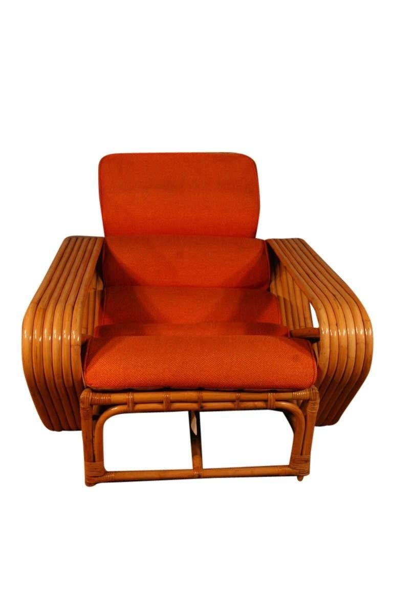 Designed in the manner of Paul Frankl, this six-strand, rattan lounge chair features square pretzel arms with matching ottoman.   Lounge chair- 29