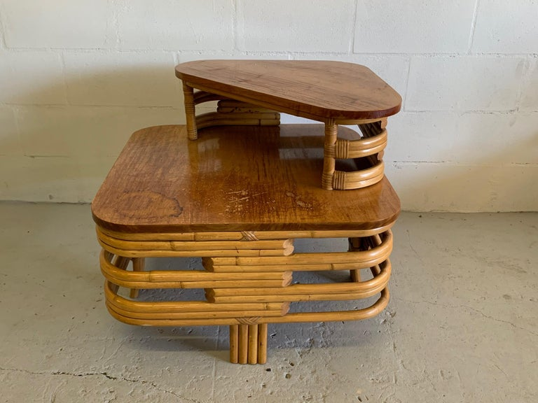 Art deco two-tiered stacked rattan side table in Paul Frankl style features bent rattan and mahogany top.   In good condition save for one area of stain at corner. Structurally very sound. Features four-strand legs at each side.