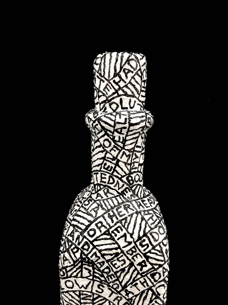 Plaster, sand, & paint on found object 11 x 2.25 x 2.25 inches  This black and white sculpture was created by Hudson Valley-based artist Paul Katz, whose process involves coating found objects in plaster, sand, & paint. The inscription which coats