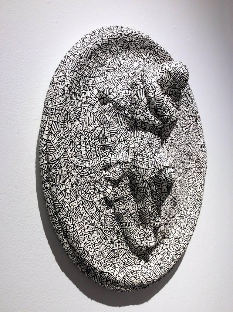 Plaster, sand, & paint on found objects 16 x 14 x 5 inches  This black and white hanging relief sculpture was created by Hudson Valley-based artist Paul Katz, whose process involves coating found objects in plaster, sand, & paint. The inscription