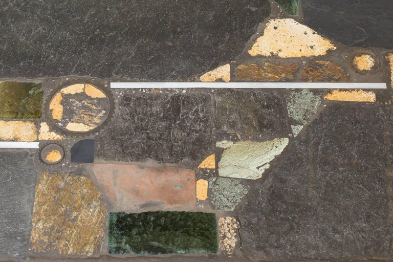 Paul Kingma mosaic stone coffee table with embedded fossil-like pieces and other stone and metal fragments. Original condition with chipping to edge of table. Enameled metal frame with visible wear consistent with age and use.