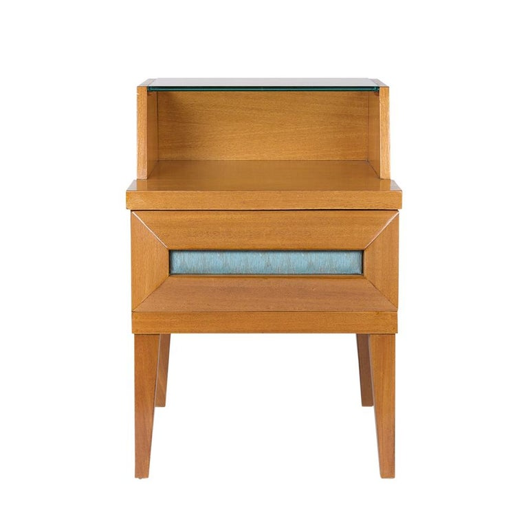 This 1950s end table by Paul Laszlo for Brown Saltman has a unique symmetrical design and features a new 3/8 clear glass top small with an open shelf below. The end table also has a single drawer with the original vinyl insert. The nightstand has