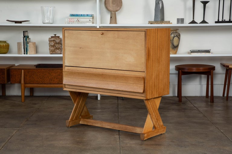 Liquor bar by Paul Laszlo for Brown Saltman, c.1957. This liquor cabinet features a bleached mahogany body and X-shaped legs with a pull down front. The top portion features vertical separation and thin lower storage drawer. The front panel drops