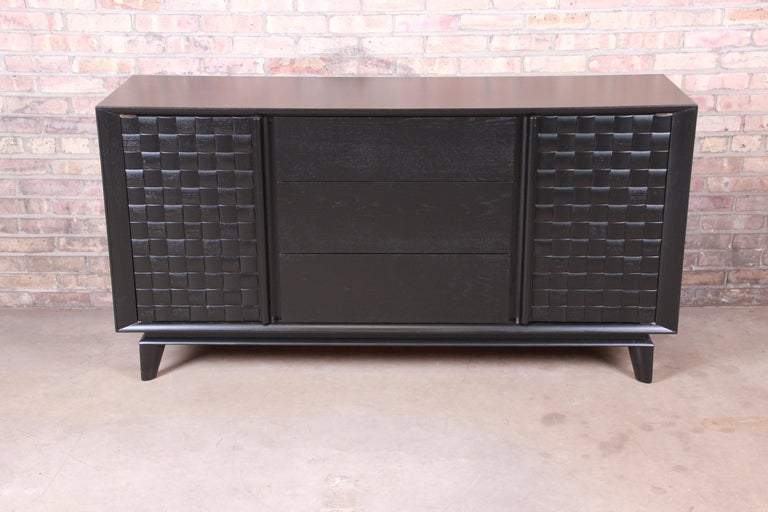 A rare and exceptional Mid-Century Modern ebonized oak sideboard credenza or bar cabinet  By Paul Laszlo for Brown Saltman  USA, 1950s  Measures: 66