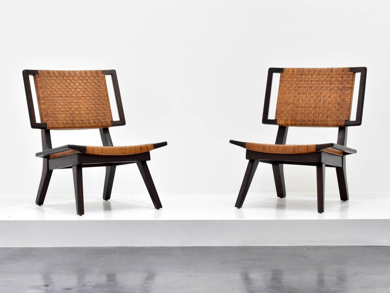 A pair of lounge chairs in the style of Paul László for Glenn of California. Dark stained mahogany and original woven rattan. Two pairs are available, as well as a settee.   Paul László is considered among the most important California-based