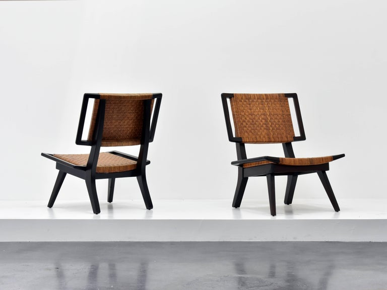 A pair of lounge chairs in the style of Paul László for Glenn of California. Dark stained mahogany and original woven rattan.  Paul László is considered among the most important California-based interior designer/architects of all time. At the