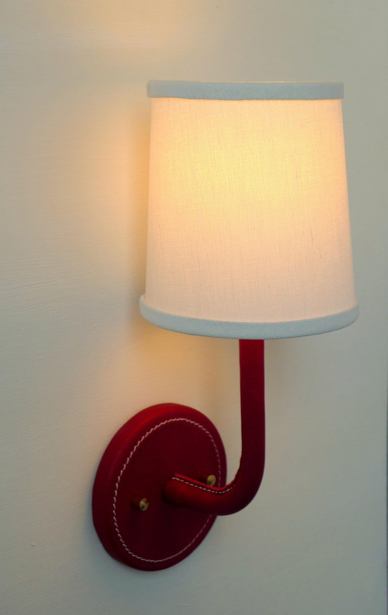 Paul Marra red leather wrapped Adnet inspired wall sconce, with top-stitched detailing. Top-stitching detail is on back plate and inner arm. Linen shade. Brass hardware. Dimensions provided are overall with shade. The shade is 4.5 top and 5.5