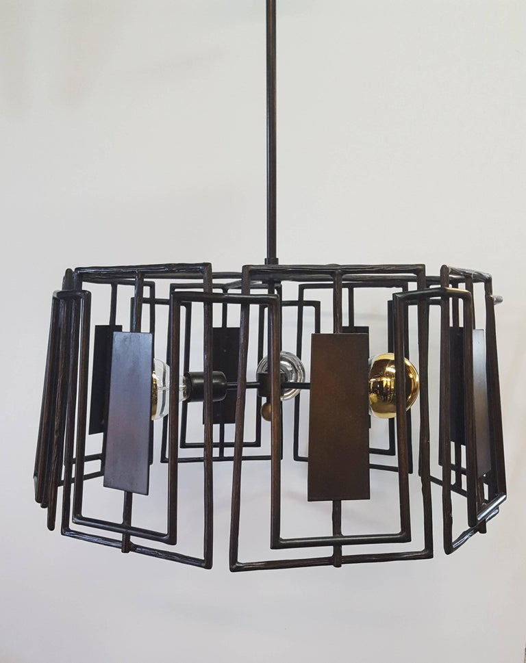 Trellis chandelier by Paul Marra. A modern fixture, in the organic modern or brutalist style. Hand-forged sculptured iron in faux bois pattern that varies throughout. Oil rubbed bronze finish. Brushed brass finial. Lamp bulbs shown as example only,