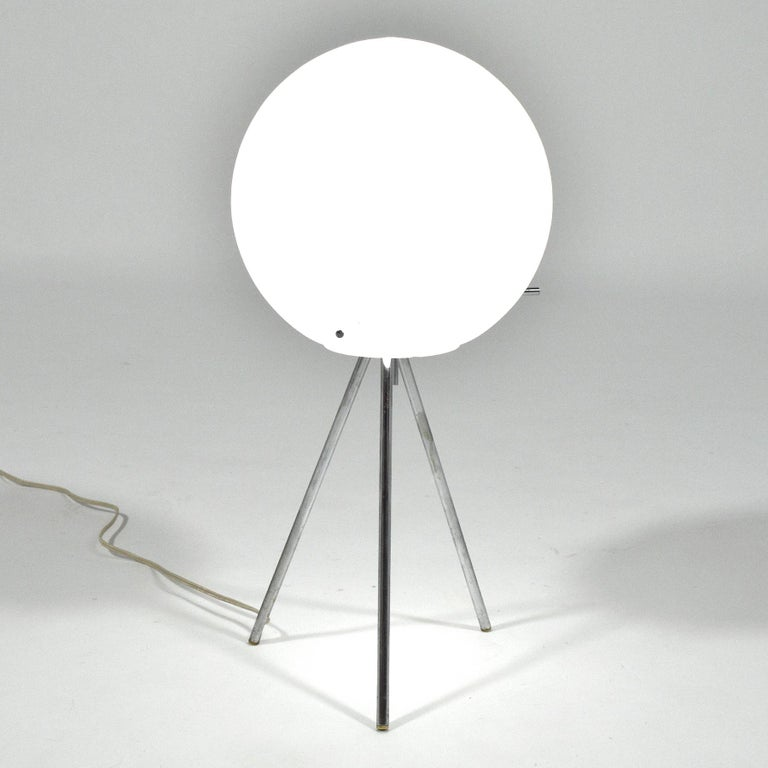 A fantastic representation of innovative lighting design and the midcentury obsession with the space race, this table lamp by Paul Mayan for Habitat features a glass globe suspended by a tripod base with arms that pierce the glass. The switch is