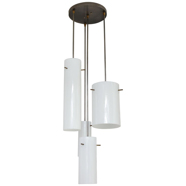 Rare hanging fixture composed of four glass cylinders of varying heights and diameters, arranged in a spiral pattern; each held by three protruding brass-plated rods. Designed by Paul Mayen and produced by Habitat, circa 1958. An artful composition,