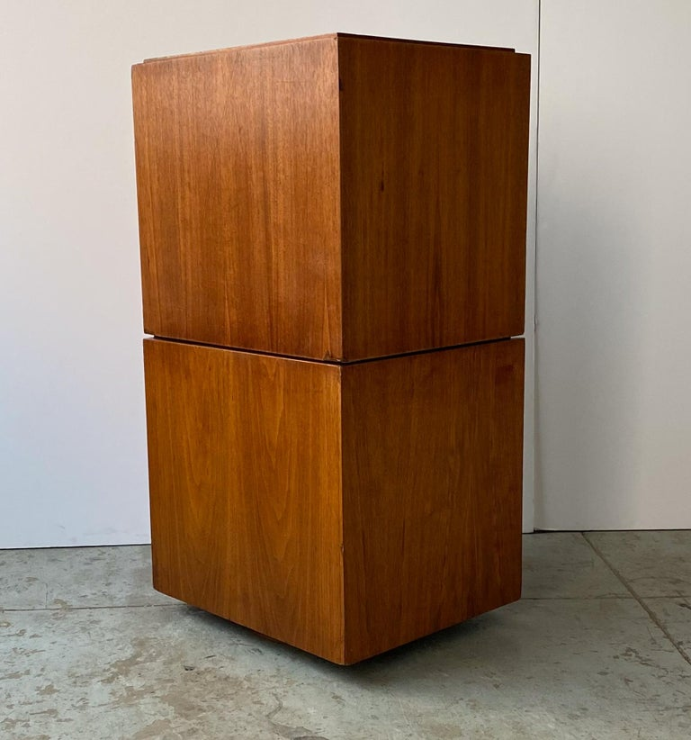Two-piece stacking and rotating storage cabinet in walnut, each with two open cubbies, designed originally for record storage by Paul Mayen and produced by Habitat/Intrex, circa 1960. The bottom component has a ball-bearing turntable underneath so