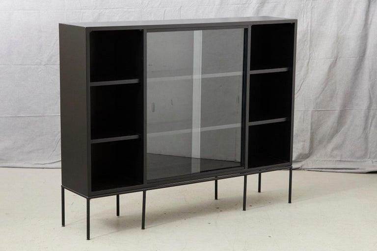 Paul McCobb for Planner Group, tall bookcase in new black finish with sliding glass doors mounted on an iron base, 1950s. Very clean, pure, graphic lines, solid maple in new black finish. The sliding glass doors are removable.