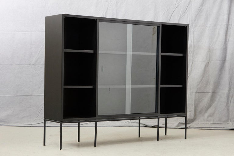 Lacquered Paul McCobb Bookcase in New Black Finish with Sliding Glass Doors on Iron Base For Sale