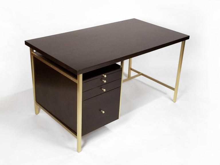 This exquisitely crafted desk was designed by Paul McCobb with a Minimalist aesthetic for his Connoisseur collection. This upscale series was produced by H. Sacks and Sons in the 1960's. Exceptional condition. The top pull engages a slide-out