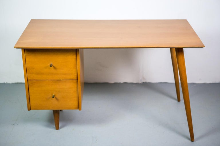 This exceptional early desk was designed by Paul McCobb and produced by Planner Group. Executed in solid maple, angular tapered legs and two desk drawers with conical brass pulls.
