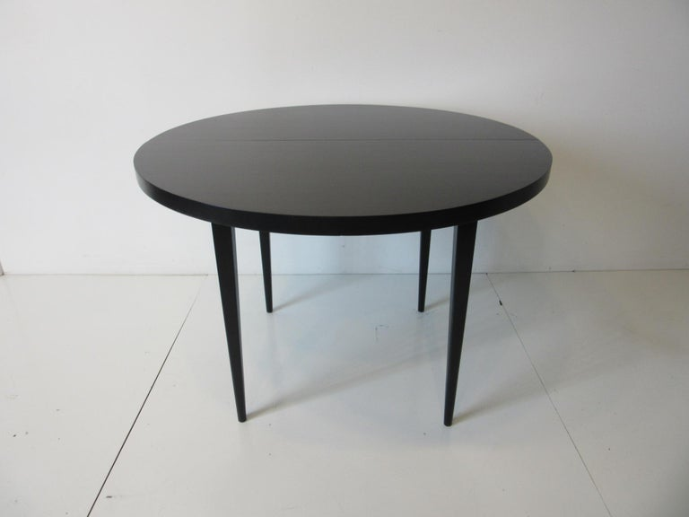 A solid maple wood midcentury dining table in satin black with two 15