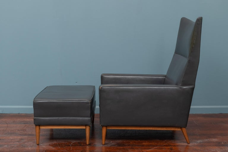 Paul McCobb design high back lounge chair and ottoman, model 314 for Custom Craft. In the original charcoal grey leather on a newly refinished stained birch base in very good usable condition with patina.