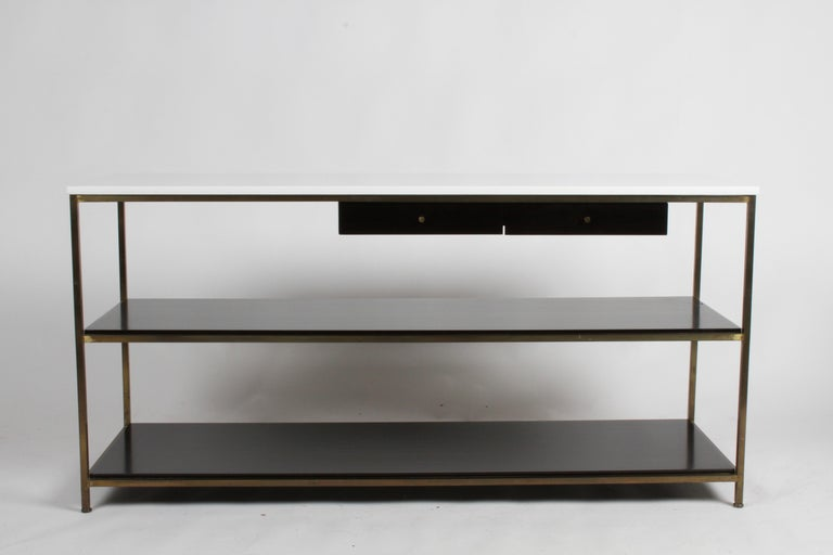 Mid-Century Modern console table or server designed by Paul McCobb for Calvin Furniture, part of his Irwin collection. Console has two drawers and two lower shelves in mahogany that have been refinished in dark espresso, and supported by brass frame