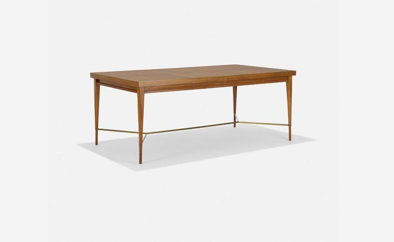 Philippine Mahogany dining table with brass X stretcher between tapered legs, designed by Paul McCobb, part of his Irwin collection for Calvin. Includes two 15
