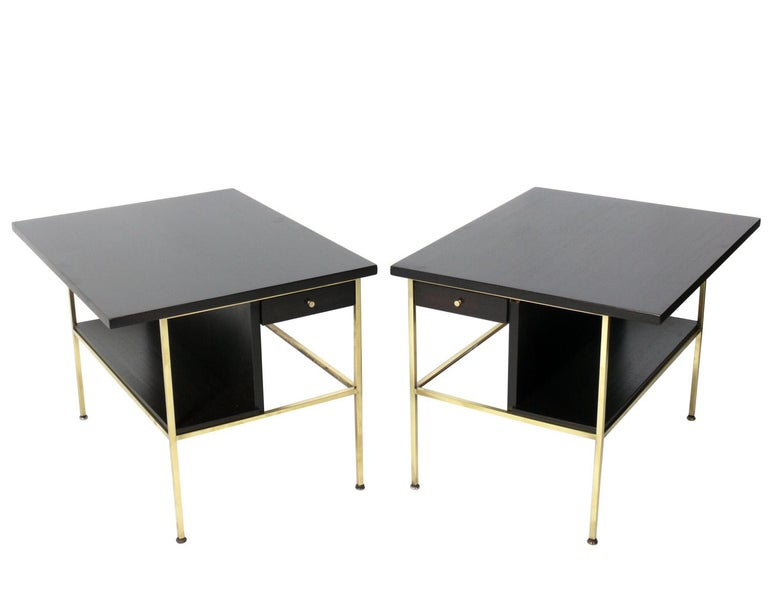 Mid-Century Modern side tables or nightstands, designed by Paul McCobb for Calvin, American, circa 1950s. Signed inside drawer. They have been completely restored in a deep brown color finish and the brass portions have been polished and lacquered.