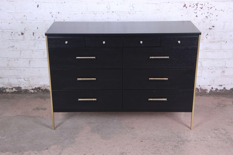 Offering a stunning ebonized Paul McCobb for Calvin Furniture ten drawer dresser. The dresser distinguished brass legs and accents offering ample room for storage. The top of the dresser offers four smaller drawers for storage and organization with