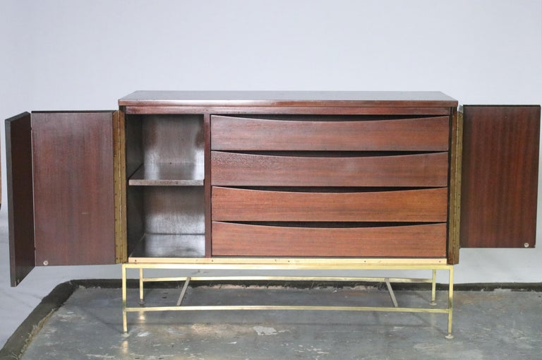 Chest of drawers or credenza / sideboard by Paul McCobb for Calvin Irwin collection in mahogany wood on brass stretchers. Bi-fold doors conceal 4- wide pull-out drawers and a cabinet with an adjustable shelf. Perfect as a buffet on a shorter wall -