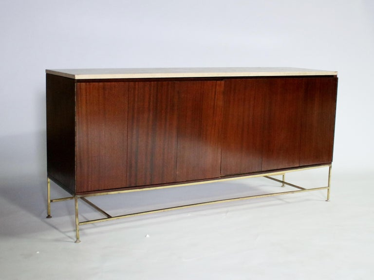 Paul McCobb from Calvin Irwin collection sideboard in original mahogany wood with brass stretchers and a travertine stone top. Accordion-style doors open to reveal a single shelf on the left side while the right side opens to 4 pull-out shelves.