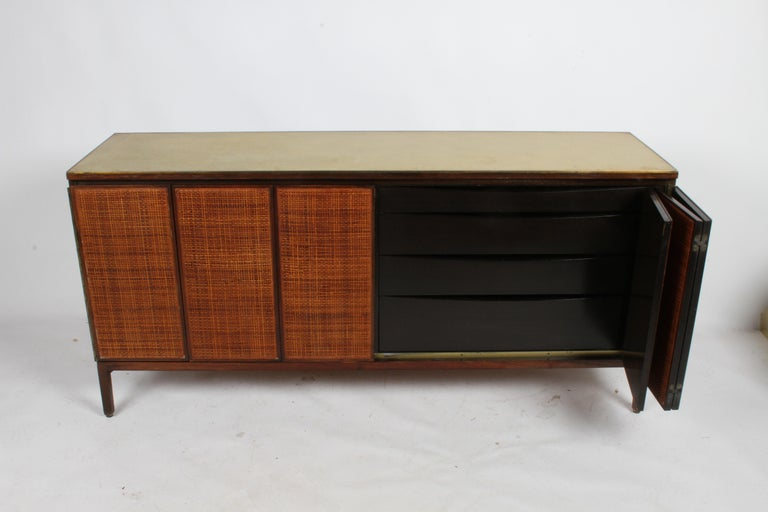 To be restored, Paul McCobb for Calvin Group dresser, sideboard or credenza with original leather top, brass edge and caned front panels. Shown in original condition, front panels to be restored and refinished, mahogany sides, legs and edges to be