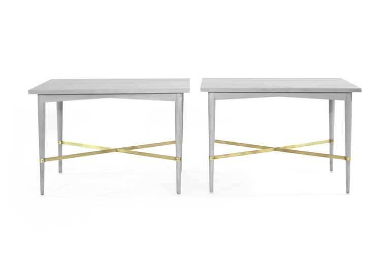 Beautiful pair of end tables newly redone in grey, featuring brass X-stretchers, designed by Paul McCobb for Directional, Connoisseur collection, circa 1950s.