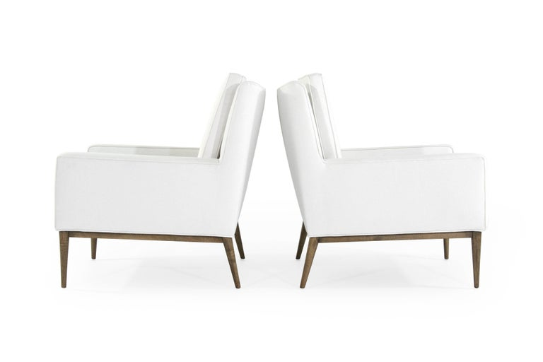 Set of iconic lounge chairs designed by Paul McCobb for Directional, circa 1950s.  Newly upholstered in white linen, beechwood bases fully restored.