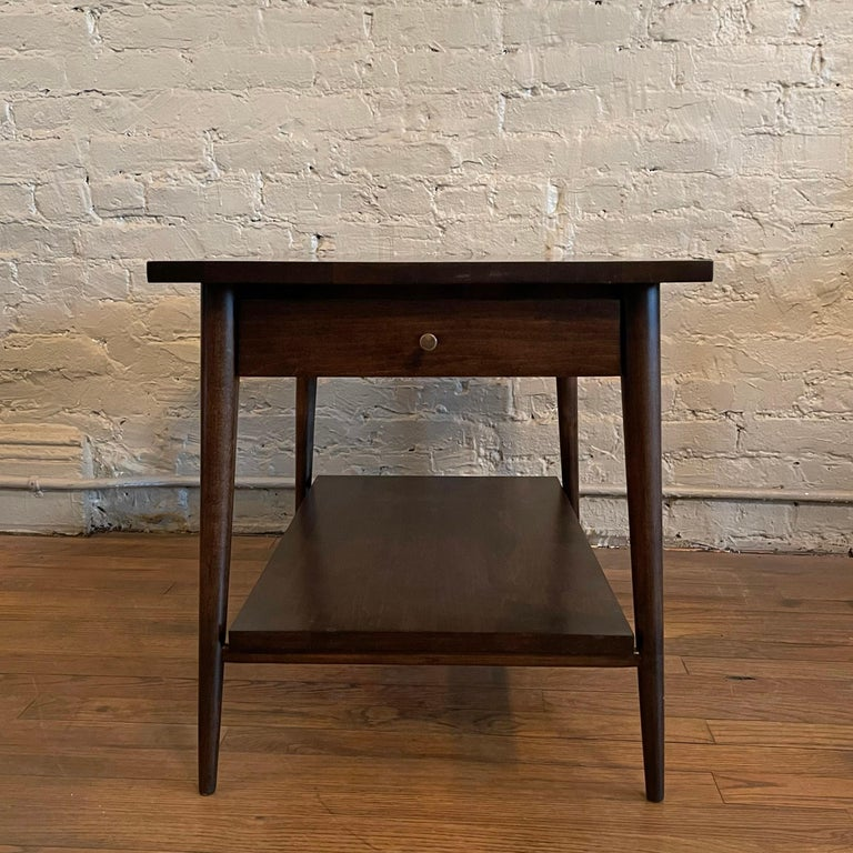 Mid-Century Modern, ebonized maple, side table with drawer by Paul McCobb for Planner Group, Winchendon, features a lower shelf and signature hourglass brass pull.