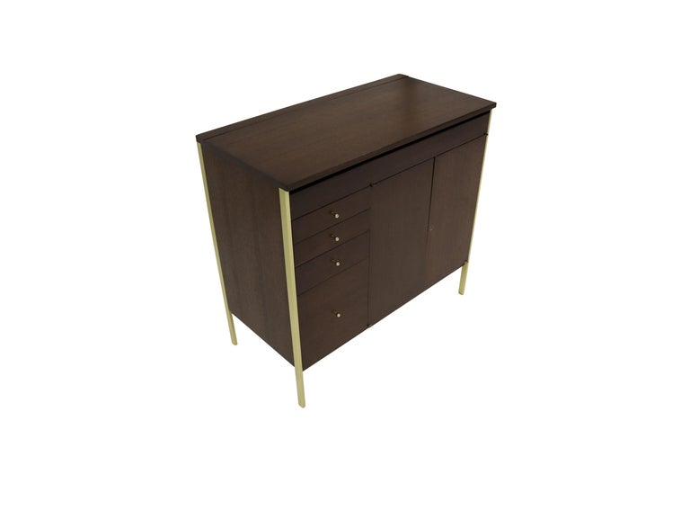 Connoisseur collection cabinet by Paul McCobb for H Sacks & Son. Fully restored. Dark walnut stained mahogany with brass legs and hardware. Four graduated drawers on the left. The two doors on the right conceal a single shelf. The top lifts to