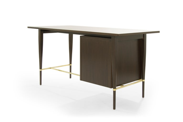 Classic desk in mahogany designed by Paul McCobb, Calvin collection, circa 1950s. Fully restored. Signature brass stretcher newly polished. Nickel-plated pulls retain some patina.