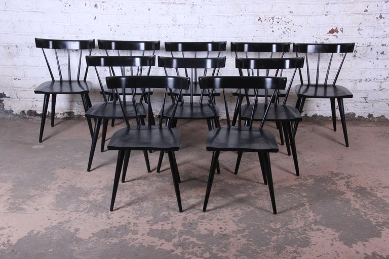 A gorgeous set of ten ebonized Mid-Century Modern spindle back dining chairs from the Planner Group line designed by Paul McCobb for Winchendon Furniture. The chairs feature solid maple construction and a beautiful black finish. An iconic McCobb
