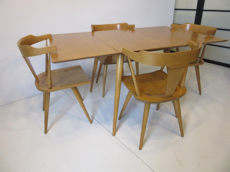 A five-piece Paul McCobb dining set including all solid maple drop-leaf table and four matching T-Back dining chairs with conical legs model # 1530. From the Planner Group collection a great midcentury design retaining the original manufactures