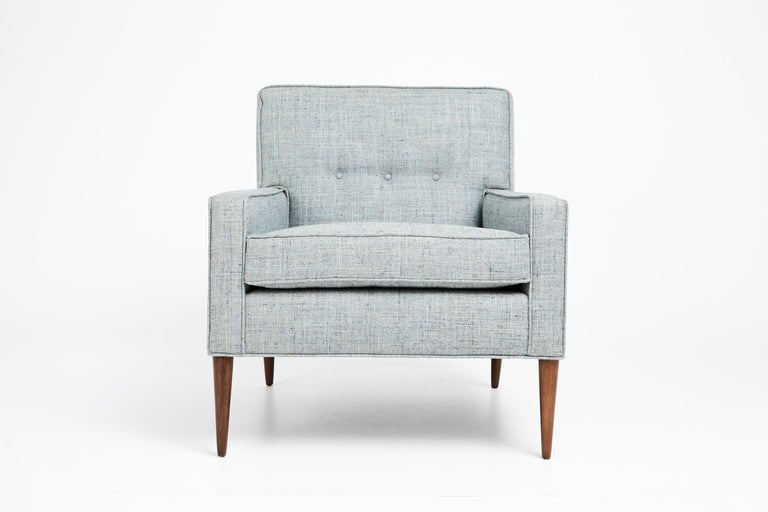 Elegant club chair designed by Paul McCobb in the mid 1950s. Classic McCobb design featuring clean lines, slender tapered legs and tufted detail on seat back. The chair has been fully restored from top to bottom. Newly reupholstered in a woven blue,
