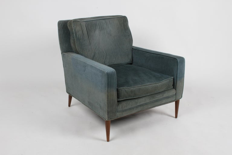 Paul McCobb Mid-Century Modern lounge chair for his Directional line with original walnut finish to maple frame on tapered legs. Older corduroy re-upholstery, upholstery and foam need updating. Front is wider than back, tapers from 30.75