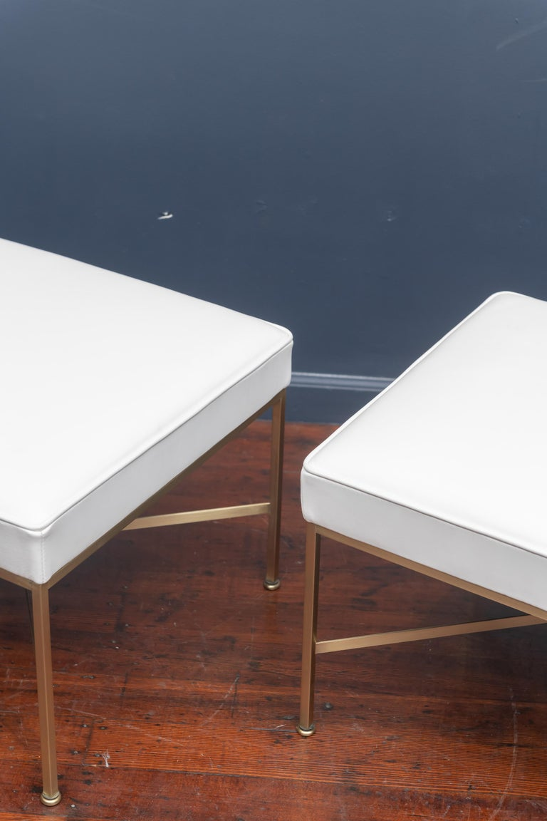 Pair of Paul McCobb X-base brass ottomans newly upholstered in off white leather.