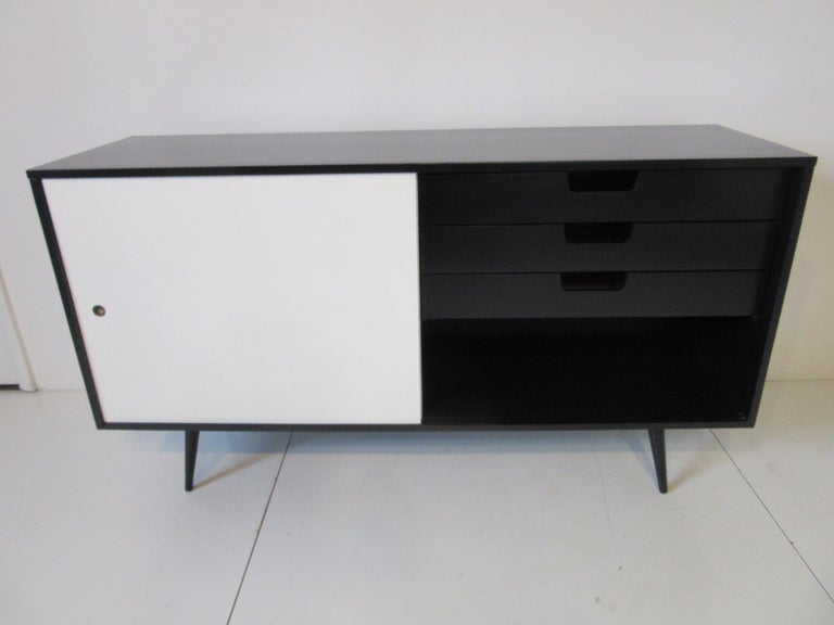 A satin black solid wood credenza with three drawers to the right side and one drawer with an adjustable shelve plus storage to the left side. Two siding white doors give this piece a tailored and thigh look, manufactured by the Winchendon furniture