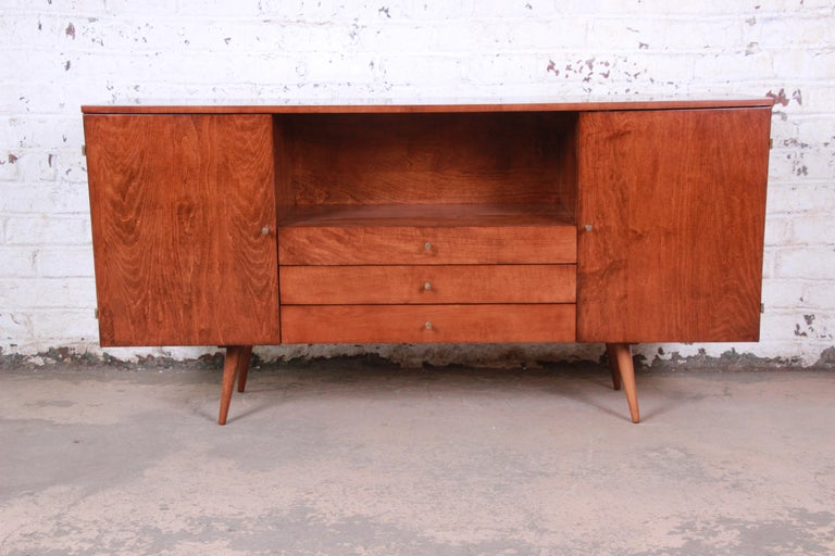A rare and exceptional Mid-Century Modern solid birch credenza or media cabinet  Designed by Paul McCobb for his Planner Group line for Winchendon Furniture  USA, 1950s  Solid birch and iconic brass drawer pulls  Measures: 66