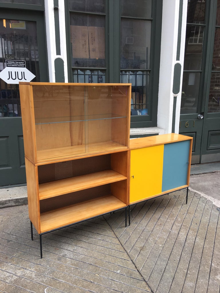 Paul McCobb 3 Piece Bookcase comprised of one cabinet with masonite sliding doors, one cabinet with glass sliding doors and glass shelf and one open unit with fixed shelf. Doors have been recovered with a period covering much like original. Can be