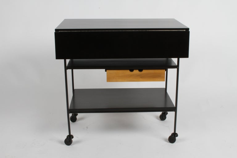 Mid-Century Modern Paul McCobb Planner Group black stained maple bar cart, painted black iron frame with expandable top, shelves and single drawer in natural maple. Each leaf is 6