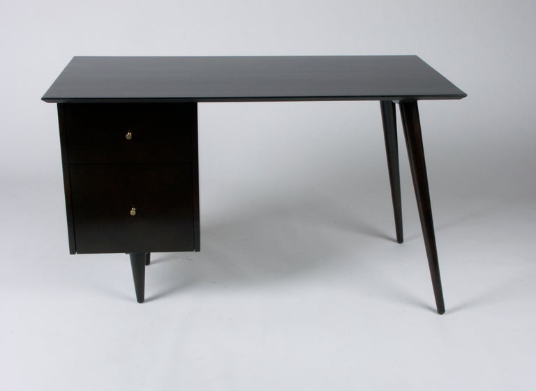 Paul McCobb Planner Group desk in dark espresso stain, with bank on drawers on left side and two tapered angular dowel legs on the right, tapered brass pulls. To be refinished in dark espresso finish, the desk shown is sold, so custom color options