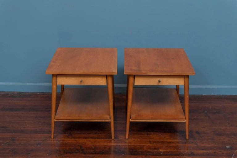 Pair of Paul McCobb design Planner Group side tables for Winchendon Furniture. Original matched pair in solid maple with brass cone shape pulls, labeled and in very good original condition.  One table has a faint shadow of a stain but still