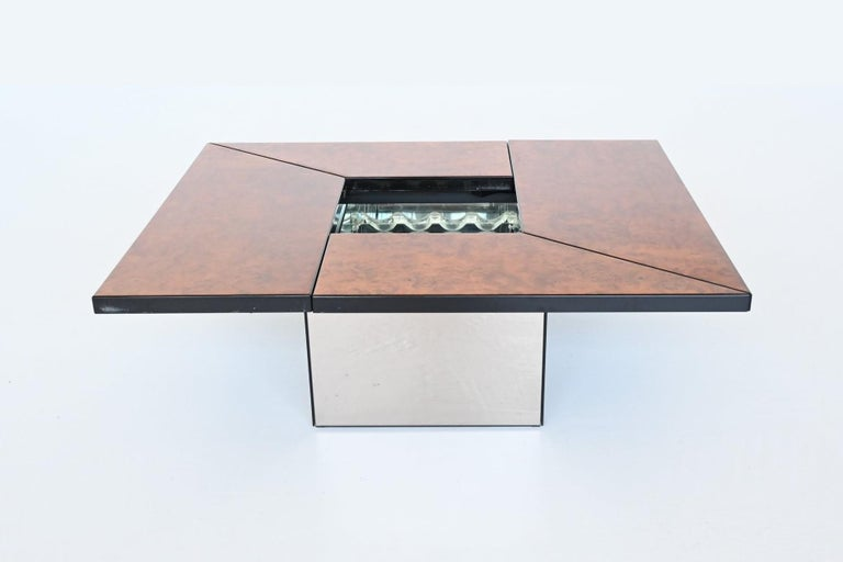 Super sophisticated stunning coffee table designed and manufactured by Paul Michel, France, 1970. This metamorphic coffee table is cleverly designed and slides smoothly open to reveal a mirrored spacious looking dry bar compartment, perfect spot to